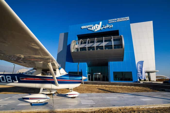A plane parked in front of the Gravity Indoor Skydiving Facility