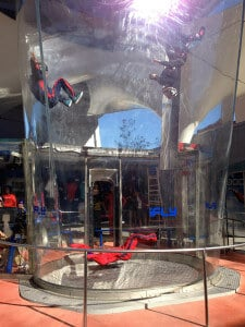 Some skydivers flying in the tunnel along the Universal Studios Citywalk.