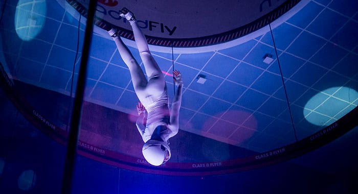 Girl in a white suit diving in the flight chamber